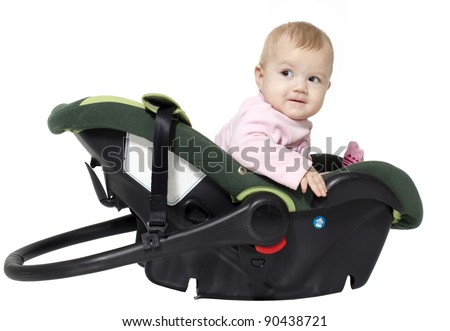 The little girl sits in an automobile cradle - stock photo