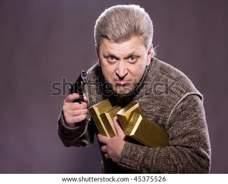 The man robber with a pistol and gold - stock photo