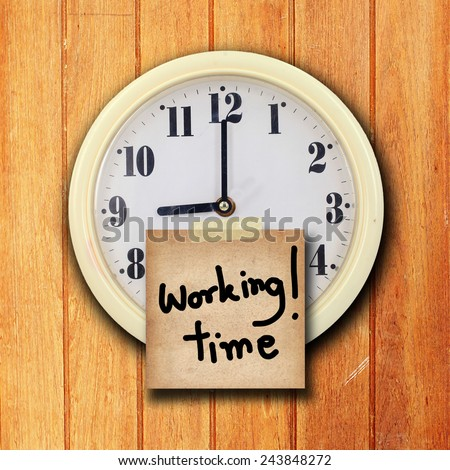 the old paper short note and text working time on the wall clock  on the wood background - stock photo