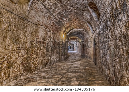 the picturesque covered alley Via delle Volte, a medieval dark passage, in Colle di Val d'Elsa, Siena, Tuscany, Italy   - stock photo