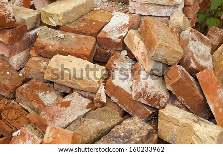 the piled old bricks of red color. were used for construction - stock photo