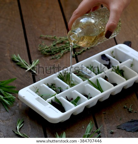 the process of pouring oil into the cell with herbs for freezing - stock photo