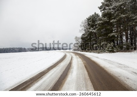 the road covered with snow to a winter season - stock photo
