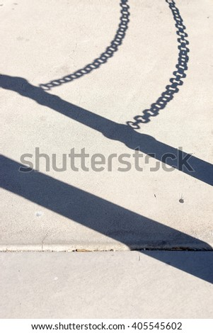 The silhouette of the shadow of a railing with chains on the asphalt of a walkway / Pathway Shadows                    - stock photo
