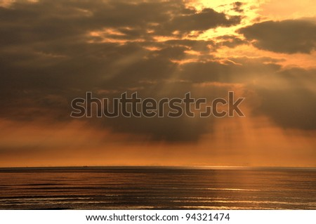 The sunrise on the sea,light through the cloud. - stock photo