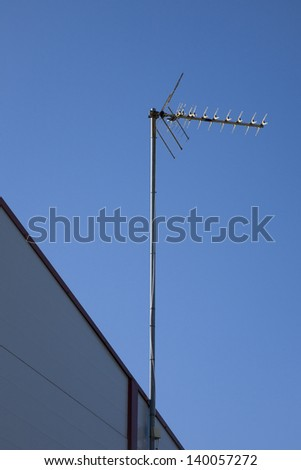 the television antenna on a house roof against the blue sky in the summer