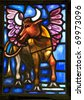 The winged ox is the evangelical symbol of St. Luke and is detail from a stained glass window from the Anglican Bermuda Cathedral built in 1866. Located in Hamilton. - stock photo