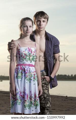 The young man and the girl stand on coast