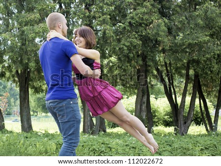 The young pair is turned in park - stock photo