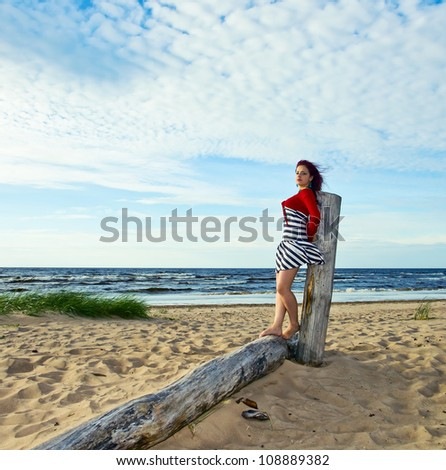 The young woman in striped dress on a beach.
