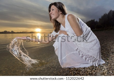 The young woman splashs water - stock photo