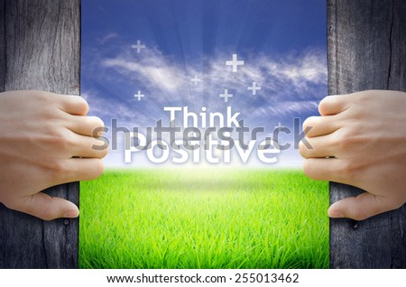 """""""Think Positive"""" Motivational quotes. Hands opening a wooden door then found a texts floating among new world as green grass field, Blue sky and the Sunrise. - stock photo"""