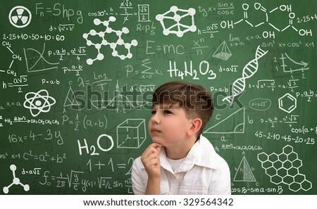 Thinking little boy with math formula writing on green  blackboard - stock photo