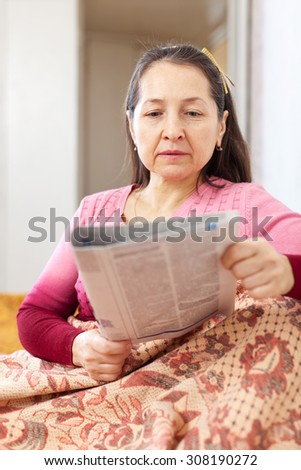 thoughtful mature woman with newspaper - stock photo