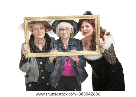 Three adult ladies in original clothes in the studio for a photo shoot. - stock photo