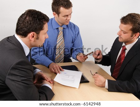 Three businessmen sitting at a table negotiating and signing a contract.