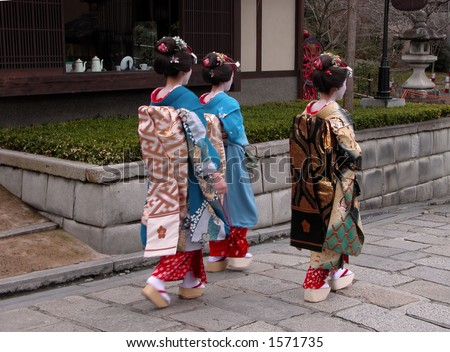 Three geisha walking in a traditional Kyoto street.There is some intended motion blur due to the stepping attitude. - stock photo