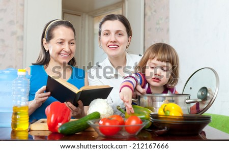 three generations of happy women cook vegetables in the kitchen - stock photo