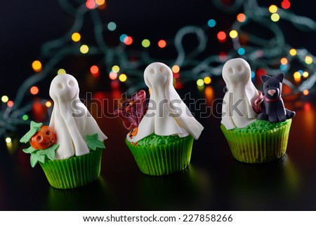 Three Halloween cupcakes decorated with sugar ghosts. Diagonal framing. - stock photo