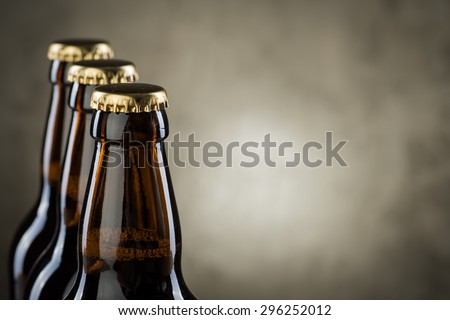 Three ice cold beer bottles in a row over the grey concrete wall background - stock photo
