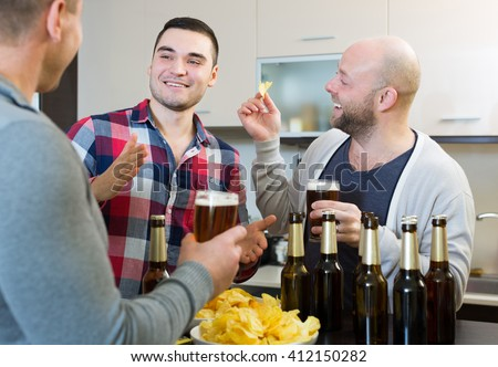 Three smiling guys drinking beer and laughing at house party - stock photo