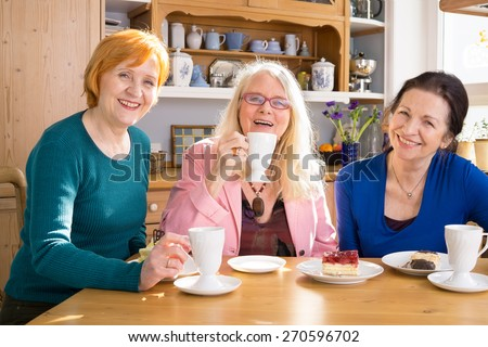 Three Smiling Mom Friends Sitting at the Wooden Table with Tasty Snacks and Looking at Camera. - stock photo