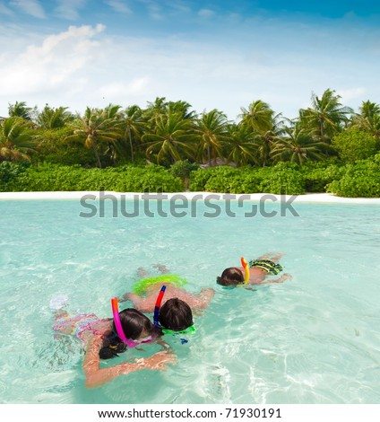 Three smiling siblings, one girl and two boys, swimming while wearing snorkeling gear in the ocean of the Maldives. - stock photo