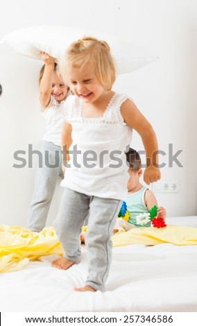 Three young children playing on  bed in  bedroom. - stock photo