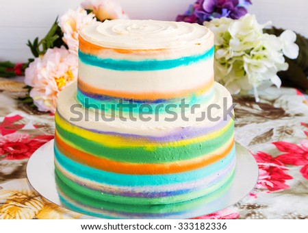 2-tiered homemade nude cake decorated with colorful stripes on floral background - stock photo