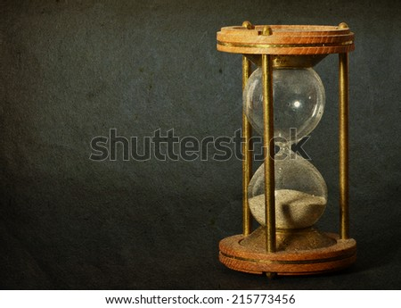 time concept with hourglass lying toned in warm dark colors on black background - stock photo