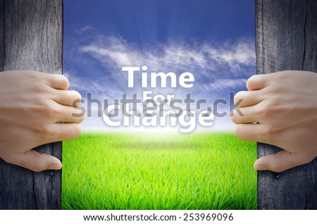 """""""Time for Change"""" Motivational quotes. Hands opening a wooden door then found a texts floating among new world as green grass field, Blue sky and the Sunrise. - stock photo"""
