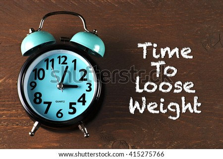 """Time For Loose Weight"" text on wooden background with clock  - stock photo"