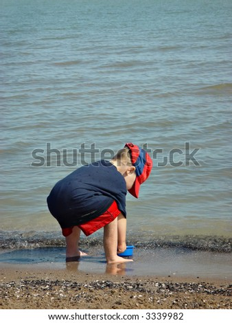 Toddler scooping up water on beach shore to make a sand castle on summer vacation