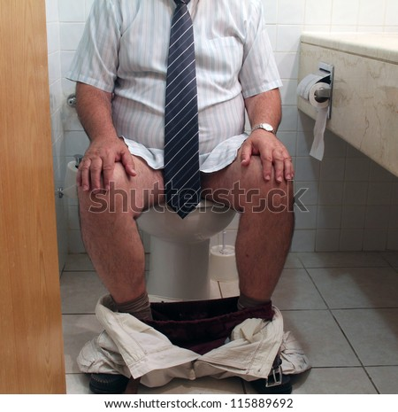 Toilet Problem. A caucasian adult man wearing white shirt and tie  on toilet seat with his trousers and boxers around his ankles. - stock photo