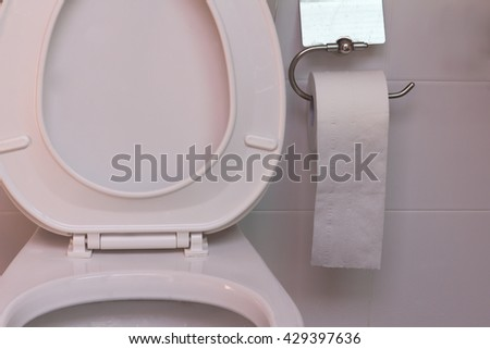Toilet seat in bathroom and toilet paper roll.Toilet, garbage, blockage. Lavatory pan, lavatory bowl,  toilet sink.Toilet paper runs out . Keep the bathroom clean . The anti-bacterial toilet .