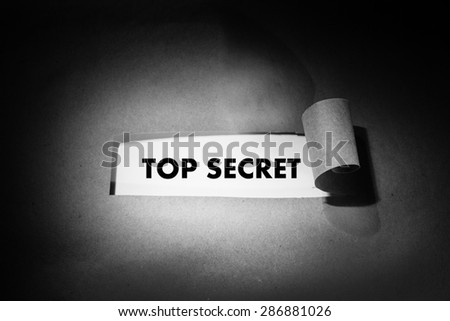 """""""Top secret"""" phrase behind torn brown paper. Black and white photo, spot light - stock photo"""