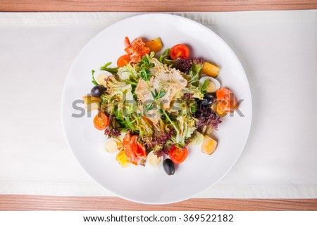 Top view Delisious salad Nicoise with salmon, arugula, lettuce, cherry tomatoes, quail eggs and olives, dressed with balsamic vinegar and olive oil  on the white plate on the served for dinner  table - stock photo