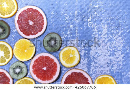 Top view. Mixed fruits background. Fresh fruit cut in half on a blue background. Grapefruit, kiwi, oranges. Top view, close-up. Ingredients for fruit salad. - stock photo