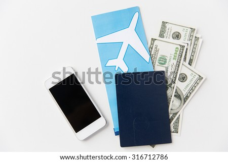 tourism, travel and objects concept - air ticket, money, smartphone and passport on table - stock photo