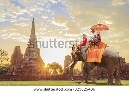 Tourists on an ride elephant tour of the ancient city in sunrise background - stock photo