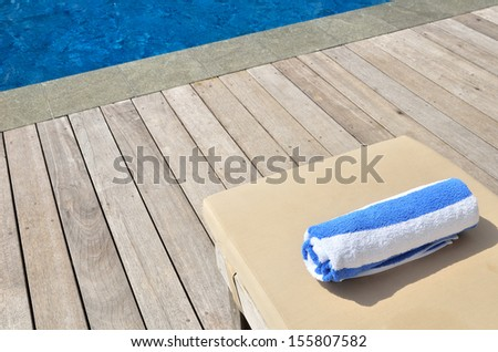 Towel on the empty sunbed by the resort pool  - stock photo