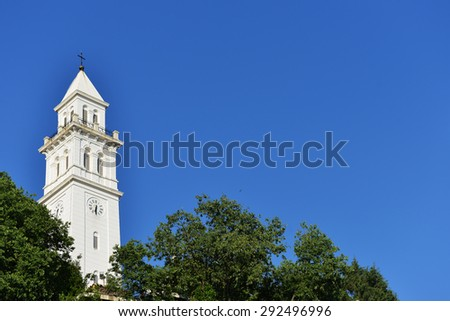 tower with clock among green trees - stock photo