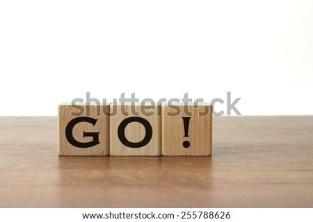 "3 Toy Wood Blocks With Letters: ""GO!"" On a Wooden Table With Light Grey Background"