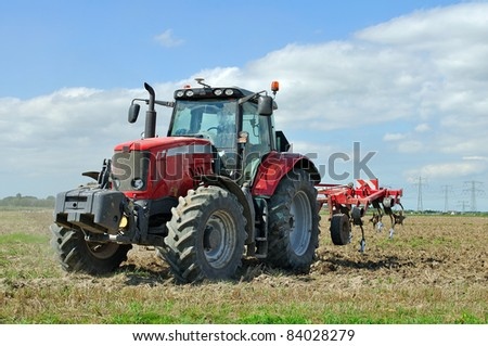 tractor during cultivation agriculture works at field with plough - stock photo
