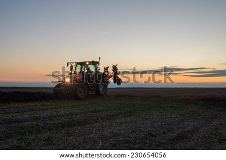 Tractor plowing at sunset - stock photo
