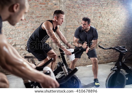 trainer gives support young man on a spinning training - stock photo