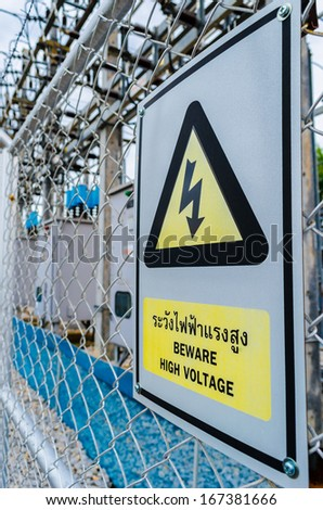 transformer station with a yellow sign beware high voltage - stock photo