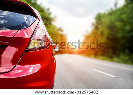 Travel concept. Red car on the road at sunset. - stock photo