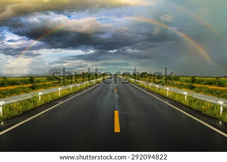 travel road asphalt  to the rainbow and rain cloud  - stock photo