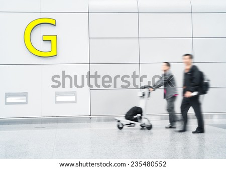 traveller walking through the walkway in airport - stock photo